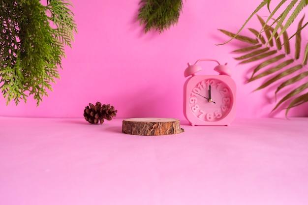 Concepto de ideas de composición con productos. madera redonda sobre un fondo rosa decorado con hojas secas, hojas de pino y reloj