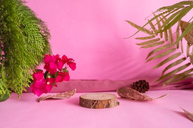 Concepto de ideas de composición con productos. madera redonda sobre un fondo rosa decorado con hojas secas, hojas verdes y tela