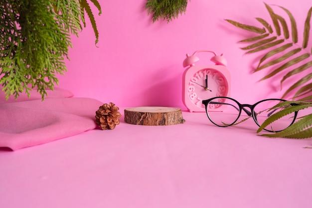 El concepto de ideas de composición con productos. madera redonda sobre fondo rosa decorado con vasos, reloj, hojas y tela.