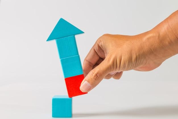 Concepto de ideas de disrupción empresarial. el hombre tirando de la mano del bloque de madera roja del bloque de madera azul