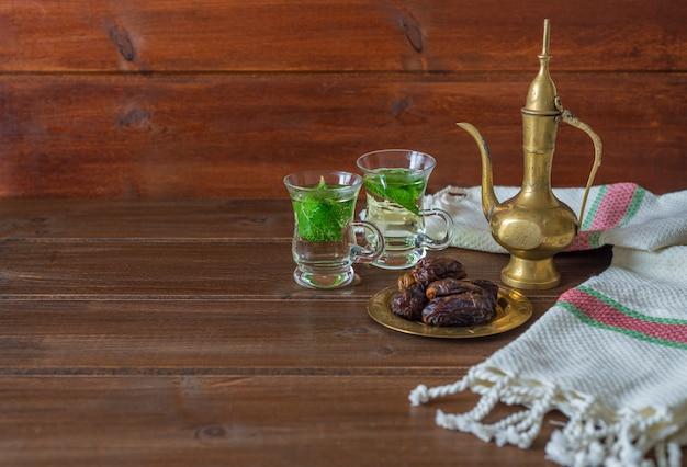 Concepto de iftar y suhoor ramadan, té mentha en tazas de vidrio y dátiles