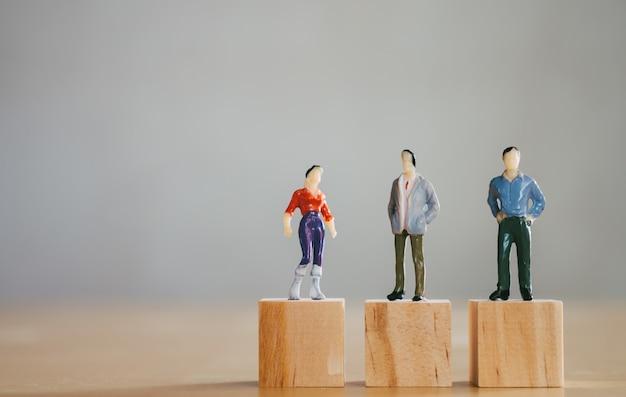 Concepto de igualdad de género, la figura femenina en miniatura se encuentra al mismo nivel que las figuras masculinas