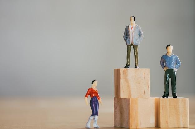 Concepto de igualdad de género, la figura femenina en miniatura se encuentra más baja que las figuras masculinas