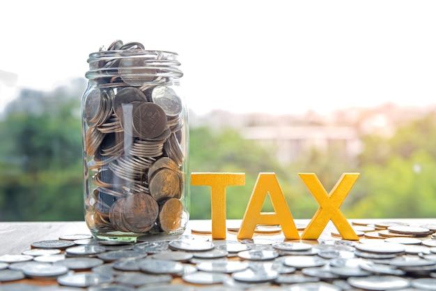 Concepto de impuesto. impuesto de palabra en monedas y tarro de moneda llena en el escritorio