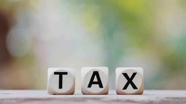 Concepto de impuestos con cubo de madera de impuestos