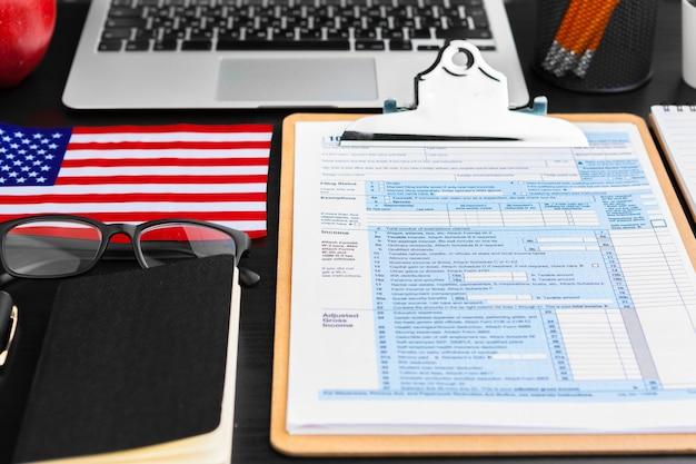 Concepto de impuestos: formulario de impuestos 1040, bolígrafo, dinero estadounidense y bandera