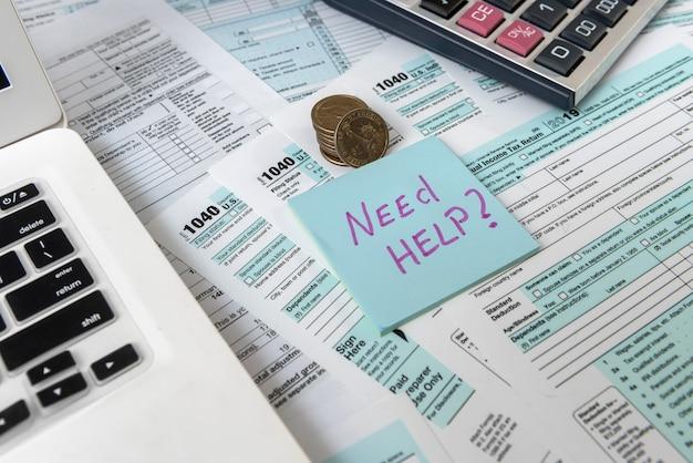 Concepto de impuestos. necesita ayuda para escribir en la calcomanía, acuñarnos, calculadora y formulario de impuestos estadounidense 1040.