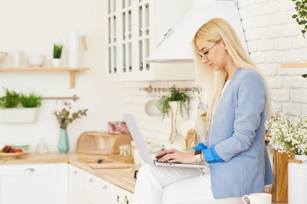 Concepto independiente. hermosa mujer de negocios en ropa casual y gafas está examinando documentos y sonriendo mientras trabajaba con una computadora portátil en la cocina