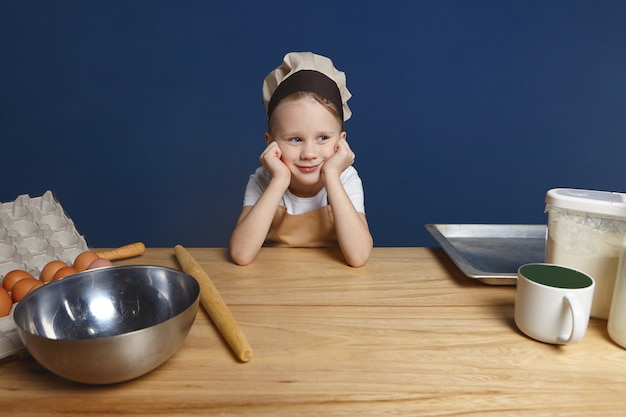 Concepto de infancia, cocina y cocina. retrato de adorable niño lindo