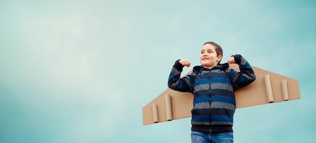 Concepto de infancia feliz sueños de volar. niño con alas de avión