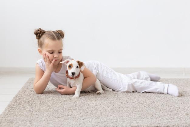 Concepto de infancia, mascotas y perros - niña pequeña posando en el suelo con cachorro.