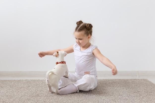 Concepto de infancia, mascotas y perros - perrito y niña con camisa blanca divirtiéndose.