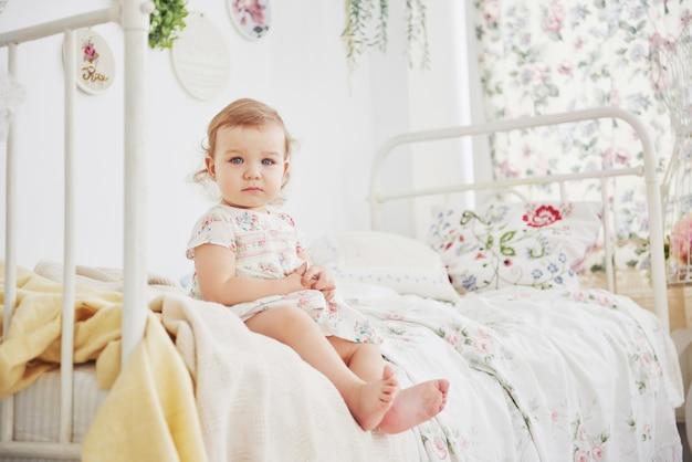 Concepto de infancia. niña en vestido lindo emplazamiento en la cama jugando con juguetes en el hogar. habitación infantil blanca vintage