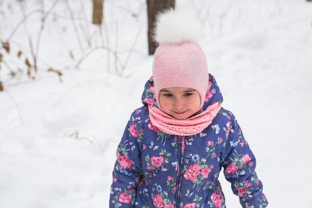 Concepto de infancia y niños - niña caminar en el invierno al aire libre