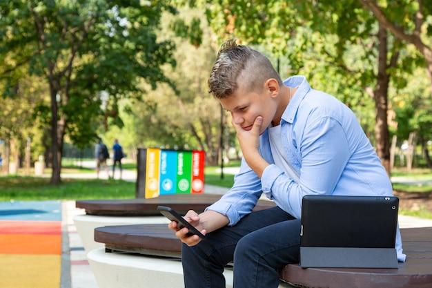 Concepto de infancia, realidad aumentada, tecnología y personas: niño con cara de desconcierto mira al teléfono inteligente al aire libre en verano