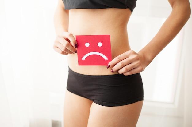 Concepto de infección y problemas vaginales o urinarios. joven mujer sostiene papel con triste sonrisa por encima de la entrepierna