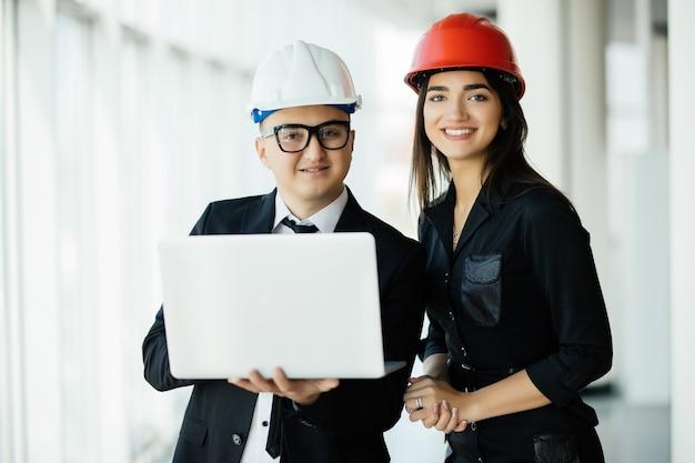 Concepto de ingeniería y arquitectura. ingenieros que trabajan en un sitio de construcción con computadora portátil, hombre arquitecto que trabaja con inspección de mujer ingeniera en el lugar de trabajo para plan arquitectónico