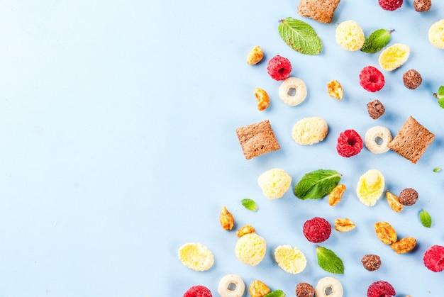 Concepto de ingredientes de desayuno saludable. varios cereales para el desayuno, frambuesas y menta sobre fondo azul, vista superior del espacio de copia
