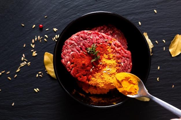 Concepto de ingredientes de preparación de alimentos carne cruda picada o molida cruda marinada con especias para comida oriental keema curry en piedra de pizarra negra con espacio de copia