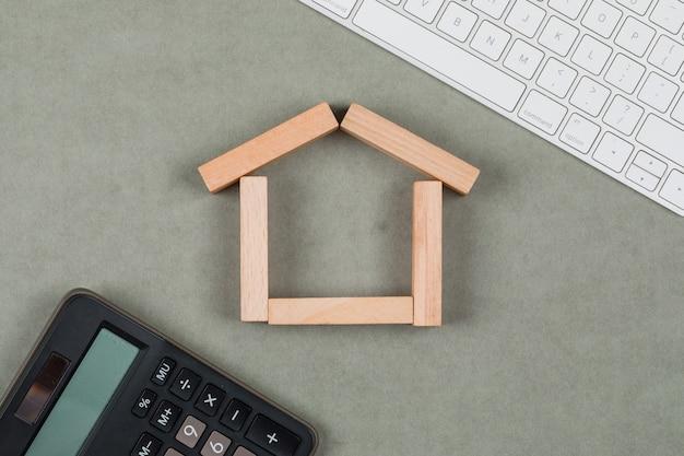 Concepto inmobiliario con bloques de madera, calculadora, teclado sobre fondo gris endecha plana.