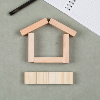 Concepto inmobiliario con bloques de madera, cuaderno, pluma en primer plano de fondo gris.