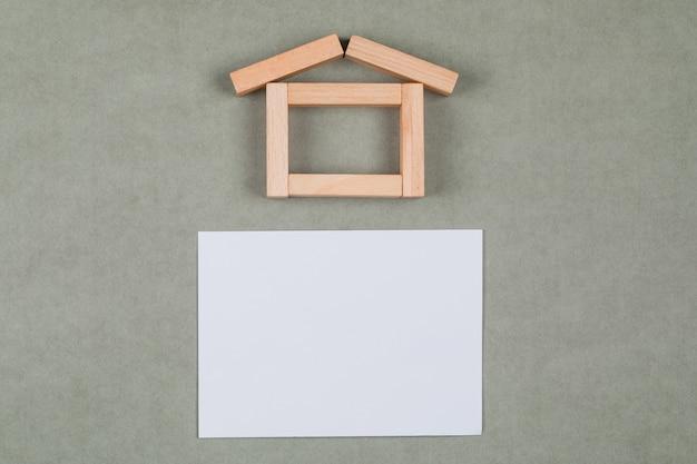 Concepto inmobiliario con bloques de madera, nota adhesiva sobre fondo gris endecha plana.