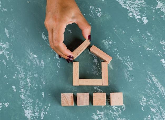 Concepto inmobiliario con bloques de madera en plano. mujer haciendo modelo de casa.