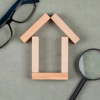 Concepto inmobiliario con casa hecha de bloques de madera, gafas, lupa en primer plano de fondo gris.