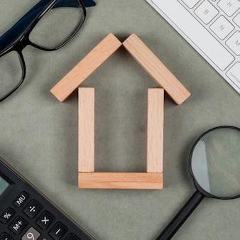 Concepto inmobiliario con casa hecha de bloques de madera, gafas, lupa, teclados en primer plano de fondo gris.
