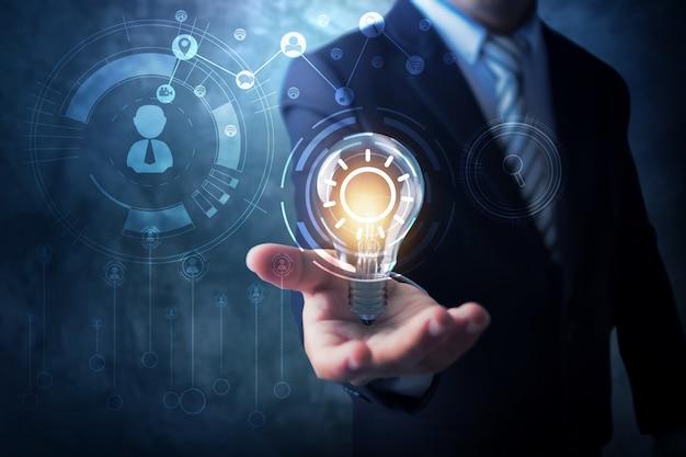 Concepto de innovación y tecnología, empresario sosteniendo sosteniendo bombilla creativa con línea de conexión para comunicarse