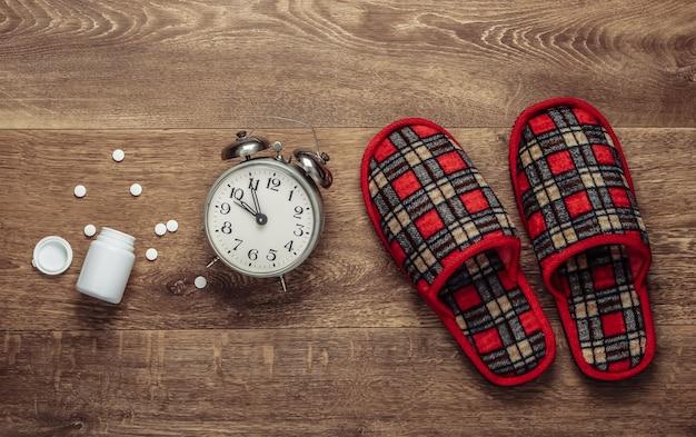 El concepto de insomnio. zapatillas de interior y despertador, pastilla en el suelo. vista superior