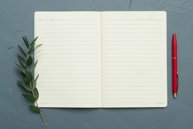 Concepto de inspiración. cuaderno abierto en blanco sobre mesa gris. pluma roja y elementos de rama de hoja de laurel. endecha plana.