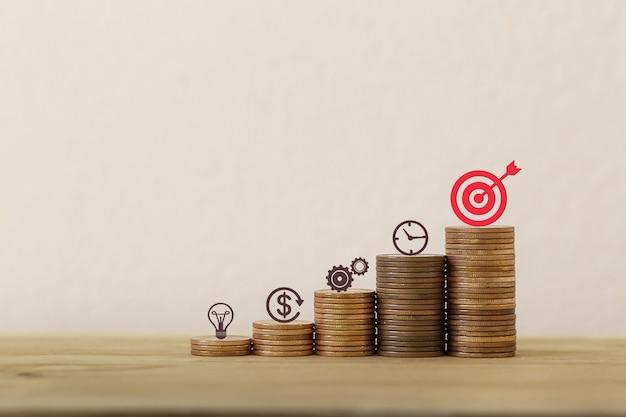 Concepto de inversión de activos de gestión financiera / objetivos: organizar el icono del plan de negocios en filas de monedas en aumento, demostrando un excelente rendimiento a través de la organización de una cartera para obtener el máximo beneficio.
