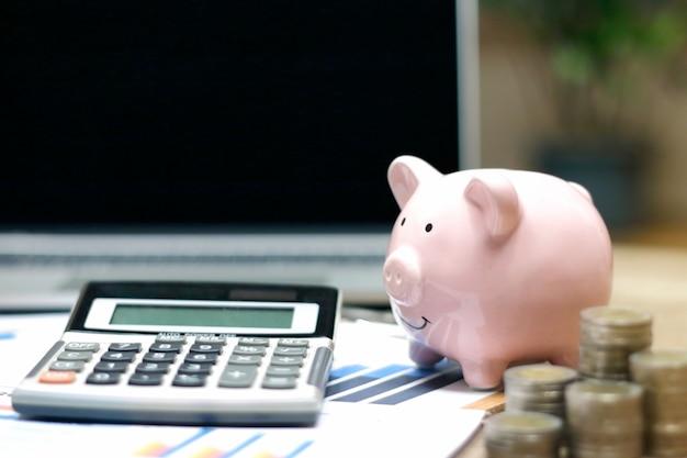 Concepto de inversión inmobiliaria o inmobiliaria portátil, pila de monedas y hucha en la mesa
