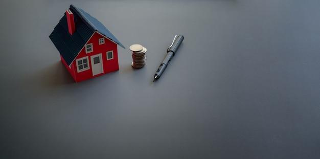 Concepto de inversión inmobiliaria y propiedad con modelo de casa pequeña