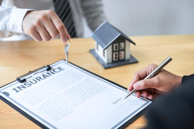 Concepto de inversión inmobiliaria y seguro de hogar, agente de venta que entrega la llave de la casa al nuevo cliente después de firmar el contrato de acuerdo con el formulario de solicitud de propiedad aprobado.