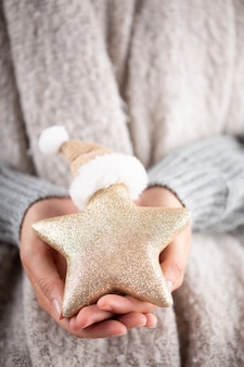 Concepto de invierno manos jóvenes sosteniendo la decoración de navidad. idea de decoración navideña. decoración navideña en manos de una mujer, fondo con bokeh dorado.
