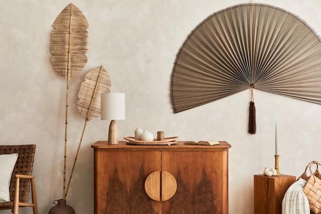 Concepto japonés de interior de sala de estar con inodoro de madera de diseño, lámpara de mesa, hoja tropical seca en jarrón, cubos, decoración, abanico japonés y elegantes accesorios personales en la decoración del hogar.