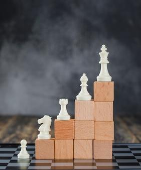 Concepto de jerarquía empresarial con tablero de ajedrez, figuras en pirámide de bloques de madera en vista lateral de mesa de madera y niebla