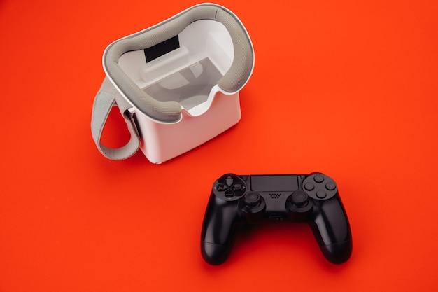 Concepto de juego. gafas de realidad virtual vr con gamepad trasero sobre fondo rojo.