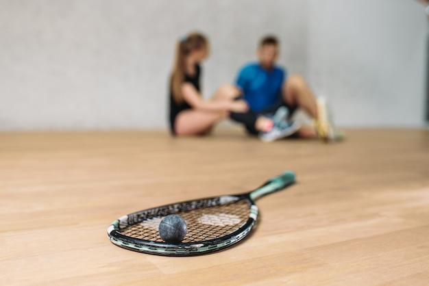 Concepto de juego de squash, raqueta con pelota, pareja joven sentada en el suelo después del entrenamiento