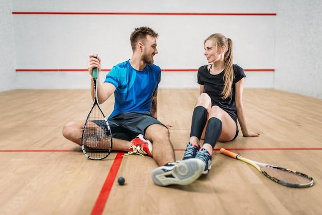 Concepto de juego de squash, raquetas con pelota, pareja joven sentada en el suelo después del entrenamiento activo