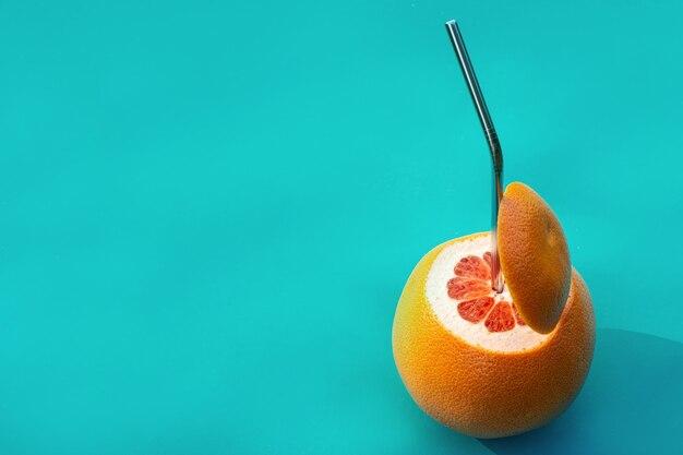 Concepto de jugo de fruta fresca natural. pomelo rojo con pajita de metal
