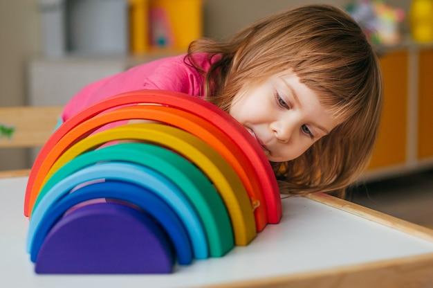 Concepto de juguetes de madera no plásticos. hermosa niña jugando con coloridos juguetes de madera arco iris en la habitación de los niños