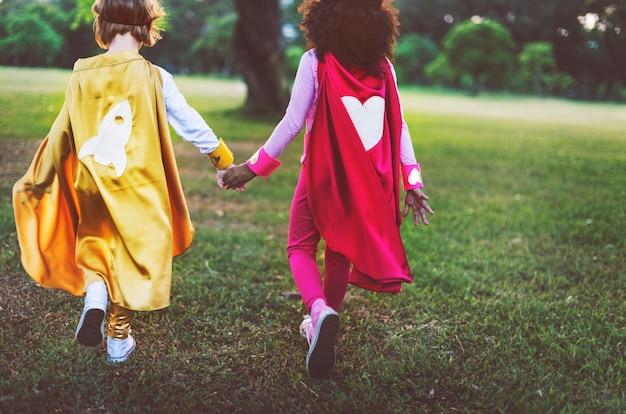 Concepto juguetón de la diversión linda de la felicidad de la amistad de las muchachas del super héroe