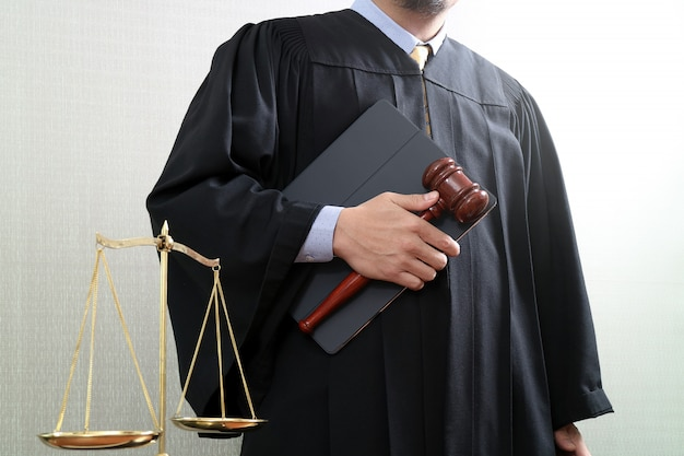 Concepto de justicia y derecho. juez masculino en un tribunal con la escala del mazo y del balance y el libro sagrado.