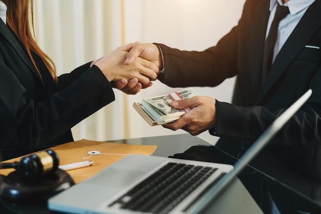 Concepto de justicia y derecho pasando dinero de soborno en el sobre en la oficina del abogado.
