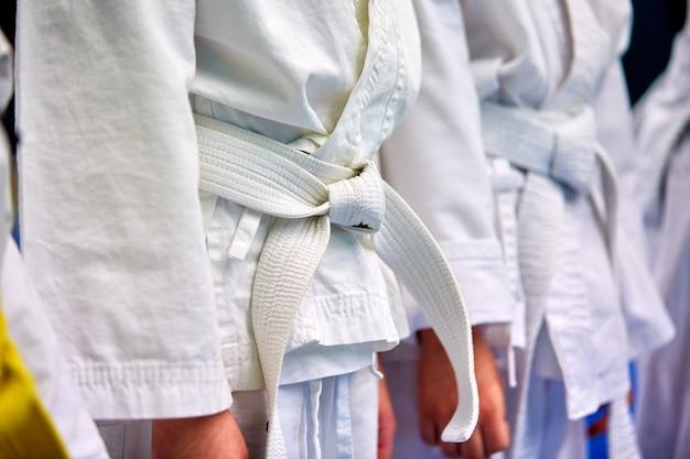 Concepto de karate, artes marciales. construcción de alumnos en la sala antes de la formación. kimono, diferentes cinturones, diferentes niveles de entrenamiento. de cerca,
