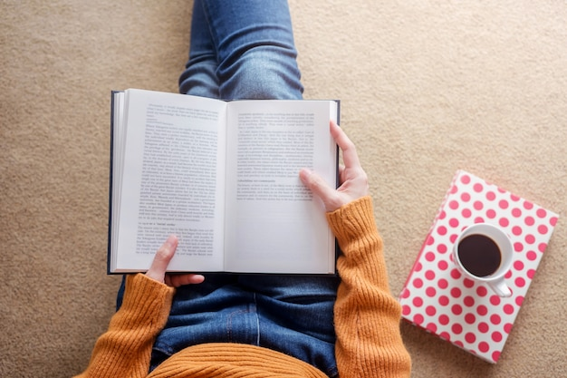 Concepto de lectura enfoque suave de mujer joven relajante por libro en casa acogedora