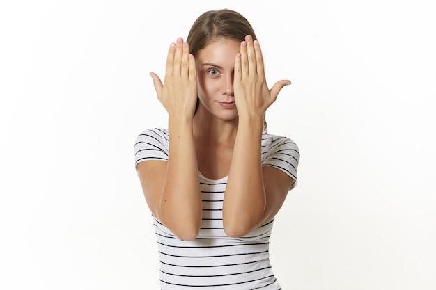Concepto de lenguaje corporal, signos, símbolos y gestos. hermosa mujer joven positiva vestida con la parte superior a rayas que cubre un ojo con la palma como si le revisaran la vista